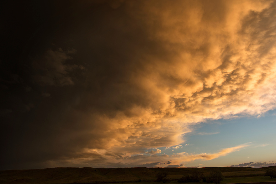 Storm clouds are illuminated by the setting sun as a thunderstorm rolls over Crow Agency in southernMontana.