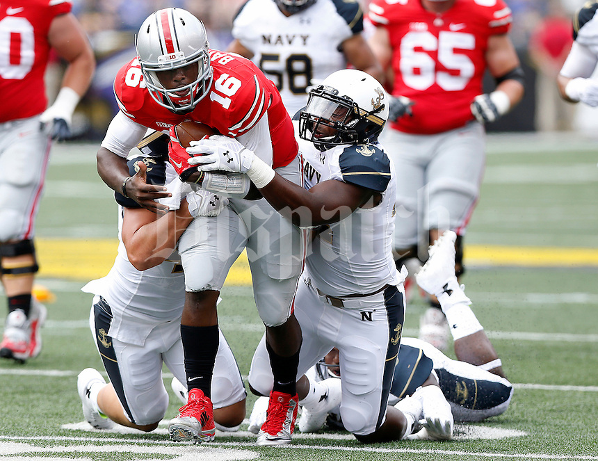 Ohio State Buckeyes quarterback J.T. Barrett (16) carries the ball up field against Navy Midshipmen linebacker Jordan Drake (13) in the 1st quarter of their NCAA game at M&T Bank Stadium in Baltimore, Maryland on August 30, 2014. (Dispatch photo by Kyle Robertson)