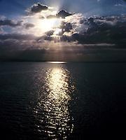 Sun bursting through the clouds reflecting on the ocean. Fiji Islands.