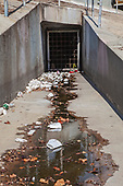 Storm Drain. Large amounts of trash and plastic refuse collect in Ballona Creek after first major rain storm of the season. Ballona Creek. Once a meandering creek, is now a concreted nine-mile flood channel that drains the Los Angeles Basin and watershed down into the Pacific Ocean, Culver City, California, USA