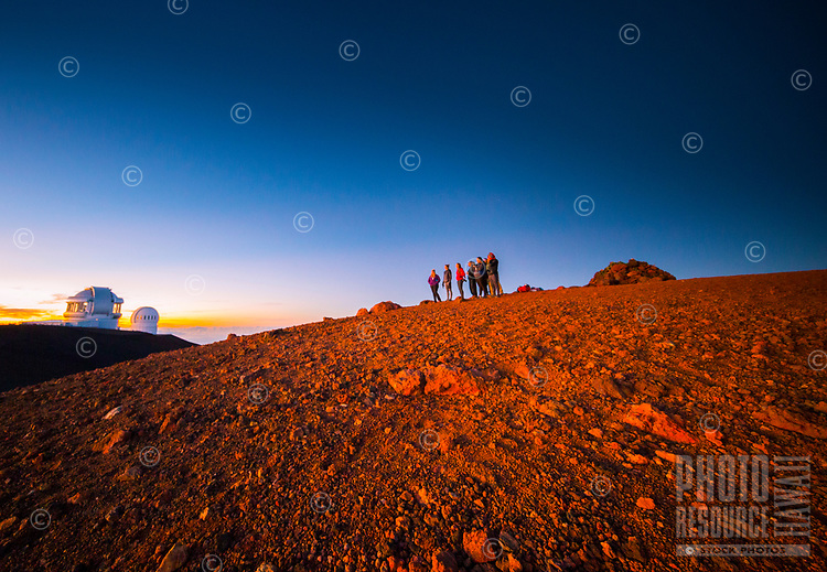 Visitors take in the sunset and view, with observatories to the left, Mauna Kea, Big Island.