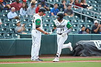 Danny Mendick (17) of the Caballeros de Charlotte shakes hands with third base coach Mark Grudzielanek (15) after hitting a home run against the Buffalo Bisons at BB&T BallPark on July 23, 2019 in Charlotte, North Carolina. The Bisons defeated the Caballeros 8-1. (Brian Westerholt/Four Seam Images)