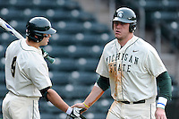 Designated hitter Blaise Salter (11) of the Michigan State Spartans is congratulated by Jimmy Pickens (9) after scoring a run in a game against the Harvard Crimson on Saturday, March 15, 2014, at Fluor Field at the West End in Greenville, South Carolina. Michigan State won, 4-0. (Tom Priddy/Four Seam Images)