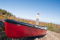 A solo canoeist portages a red canoe over a hill with views of Lake Superior below.