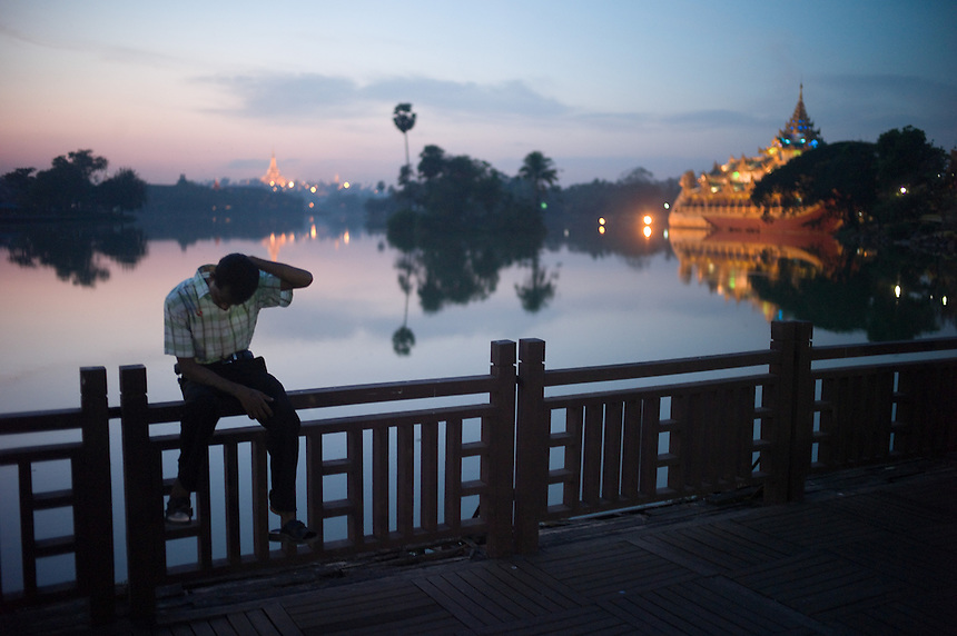 As the evening sun falls on Kandawgyi Lake near downtown Yangon (Rangoon), a passer by rests on a fence rail. At center the historic Shwedagon Paya glows The historic glows in the background, along with the government-financed Karaweik dinner theater which replicates a royal barge floating on the lake. Yangon, Union of Myanmar (Burma), Nov. 26, 2009...EDS: Not for syndication nor redistribution. Web slide show only. Please do not strip metadata for Web use.