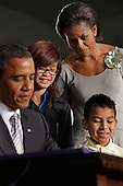 United States President Barack Obama (L) signs the Healthy, Hunger-Free Kids Act of 2010 with first lady Michelle Obama (R), 3rd-grader Luis Avilar-Rurcios (2nd R) and 7th-grader Tammy Nguyen (2nd L) at Harriet Tubman Elementary School, Monday, December 13, 2010 in Washington, DC. In an effort to provide children with better school lunches and breakfasts, the new law puts $4.5 million in the hands of child nutrition programs, sets nutrition standards on school vending machines, helps create school gardens and makes sure that quality drinking water is available during meal times. .Credit: Chip Somodevilla - Pool via CNP