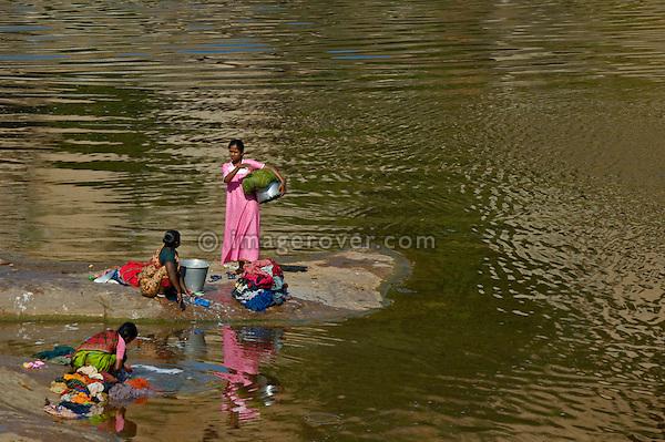 Indian women washing clothes by hand in the Tungabhadra river. Hampi, Karnataka, India 2005.