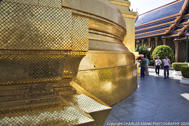 Visitors are dwarfed by the scale of the gold plated stupa in Wat Phra Kaew at the Grand Palace in Ko Rattanakosin in downtown Bangkok.