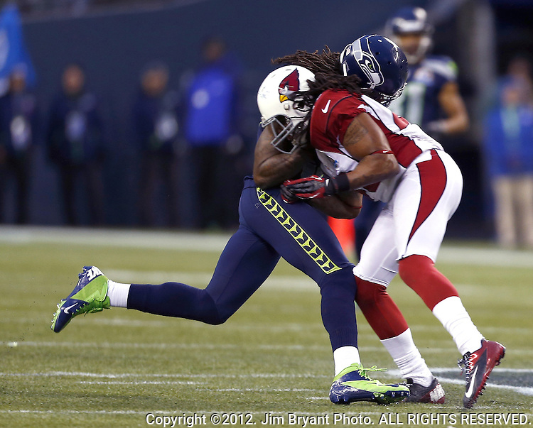 Seattle Seahawks wide receiver Sidney Rice is hit by Arizona Cardinals safety Rashad Johnson after catching a pass for 17 yards at CenturyLink Field in Seattle, Washington on  December 9, 2012.  The Seahawks beat the Cardinals 58-0.  ©2012. Jim Bryant Photo. All Rights Reserved.