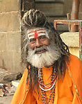 The beautific face of a Vshnu Holy Man in Varanasi by the Ganges River. The Holy Man wears the tilaka marks of a religious man, a graying beard and dreadlocks and the traditional orange robe. He has the most smile and knowing-eyes.