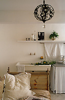 An informal  kitchen area at one end of the living room has a free-standing enamel sink