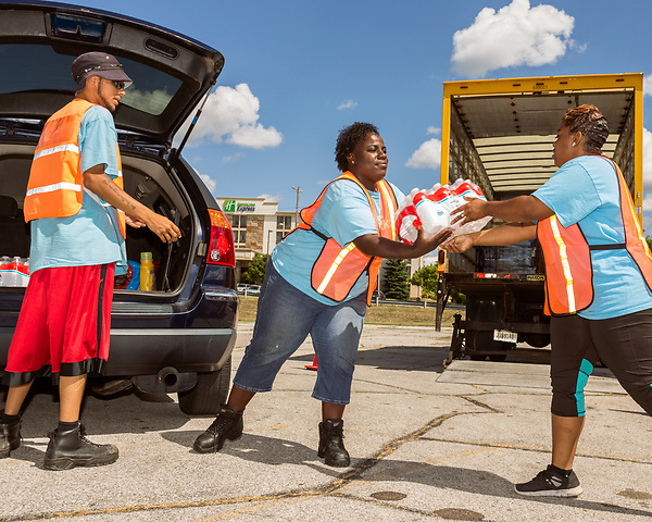 August 6, 2016. Flint, Michigan.<br />  (left to right) Robert Burns, Tabitha Coffey and Reekila Dudley load a Flint residents car with bottled water.  They are part of the Michigan Works program with puts Flint residents to work while giving them on the job training. <br />  Although Flint city government says their water is safe to drink when filtered properly, many residents still rely on bottled water for drinking and bathing. Through federal emergency funds, the state distributes 1000's of cases of bottled water nearly every day to Flint residents.<br />  In April 2014, the city of Flint switched its water source from the Detroit Water and Sewerage Department to using the Flint River in an effort to save money. When the switch occurred, the city failed to have corrosion control treatment in place for the new water. This brought about a leaching of lead from pipes into the water, increasing the lead content in the drinking water to levels far above legal limits. After independent sources brought this to light, the city admitted the water was unsafe and legal battles have ensued between resident and the local and state governments.