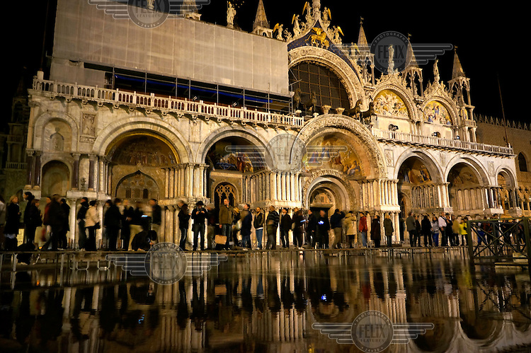 Tourists cross a boardwalk outside St Mark's Cathedral after a high tide has flooded St Mark's Square.