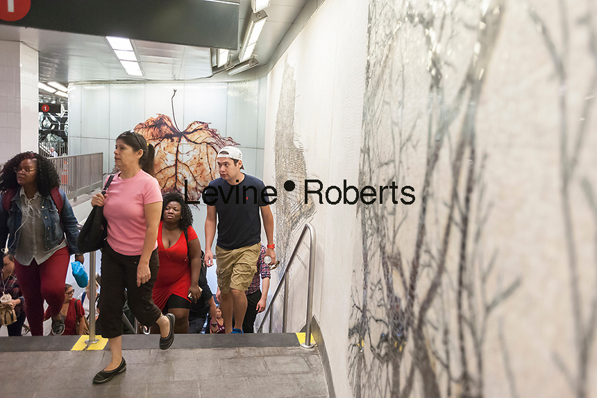 Passengers arrive and depart the newly restored South Ferry subway station in New York on re-opening day Tuesday, June 27, 2017. The restored station was closed after catastrophic damage by Superstorm Sandy with an estimated 15 million gallons of water flooding the terminal which cost $545 million and was only open three years. The $340 million in repairs were finished today nearly five years after Superstorm Sandy. In the interim the Number One train used the quirky old South Ferry loop which only accommodated the first five cars of a ten car train.  (© Richard B. Levine)