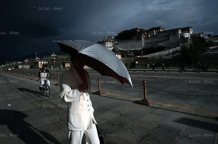 A woman walks past the Potala Palace in Lhasa.