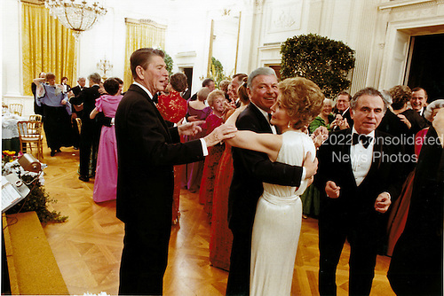Frank Sinatra dances with First Lady Nancy Reagan in the East Room of the White House in Washington, D.C. on February 6, 1981 as United States President Ronald Reagan attempts to cut-in at the President's birthday party.<br /> Mandatory Credit: Michael Evans - White House via CNP
