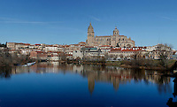 Panoramic view, Cathedral, Salamanca, Spain, pictured on December 18, 2010 in the afternoon, with the Bell Tower and Cupola towering over the surrounding houses, and reflected in the Tormes river. Salamanca, Spain's most important University city,  has two adjoining Cathedrals, Old and New. The old Romanesque Cathedral was begun in the 12th century, and the new in the 16th century. Its style was designed to be Gothic rather than Renaissance in keeping with its older neighbour, but building continued over several centuries and a Baroque cupola was added in the 18th century. Restoration was necessary after the great Lisbon earthquake, 1755. Picture by Manuel Cohen