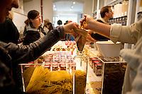 """Berlin, Besucher fuellen am Samstag (13.09.2014) im neueroeffneten Supermarkt """"Original Unverpackt"""", im dem Lebensmittel und Haushaltsprodukte ohne Verpackungen verkauft werden, Nudeln in iene Glasflasche. Der Laden in der Wienerstrasse in Berlin Kreuzberg wurde ueber Crowdfunding finanziert. Foto: Steffi Loos/CommonLens"""