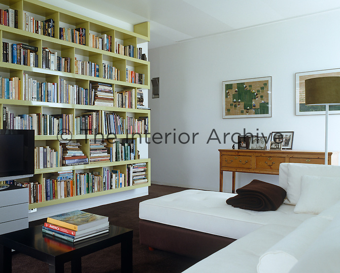 The bookshelf in the study echoes the shape of the exterior of the house