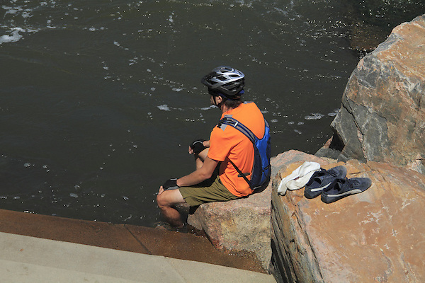 Male biker sitting and resting along river in Boulder Creek, Boulder, Colorado. .  John offers private photo tours in Denver, Boulder and throughout Colorado. Year-round Colorado photo tours.