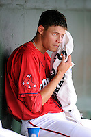 Starting pitcher Trey Ball (32) of the Greenville Drive dries off in the dugout during his first Class A appearance against the Lexington Legends on Sunday, April 27, 2014, at Fluor Field at the West End in Greenville, South Carolina. Ball was the No. 1 pick of the Boston Red Sox in the 2013 First-Year Player Draft. He is the No. 10 Red Sox prospect, according to Baseball America. Greenville won, 21-6, and Ball got the win. (Tom Priddy/Four Seam Images)