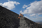 Group of backpackers climb the active Cerro Negro volcano, holding wooden sleds and carrying orange protective suits, Nicaragua