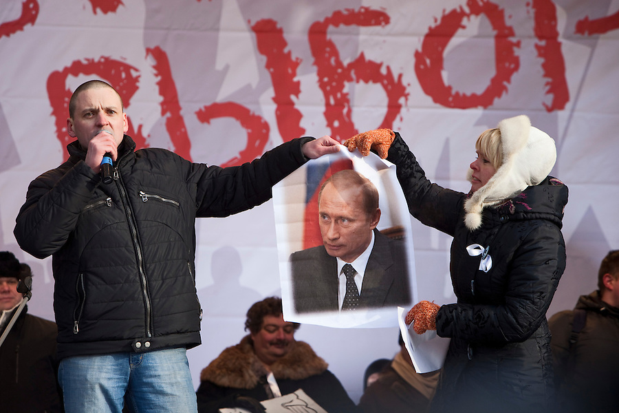 Moscow, Russia, 04/02/2012..Left Front leader Sergei Udaltsov and ecological activist Yevgenia Chirikova hold a poster of Russian Prime Minister Vladimir Putin before Udaltsov tore it to shreds and through it to the crowd, as tens of thousands of demonstrators march in central Moscow and protest against election fraud and Prime Minister Vladimir Putin in temperatures of -20 centigrade. Organisers claimed an attendance of 130,000 despite the bitter cold.