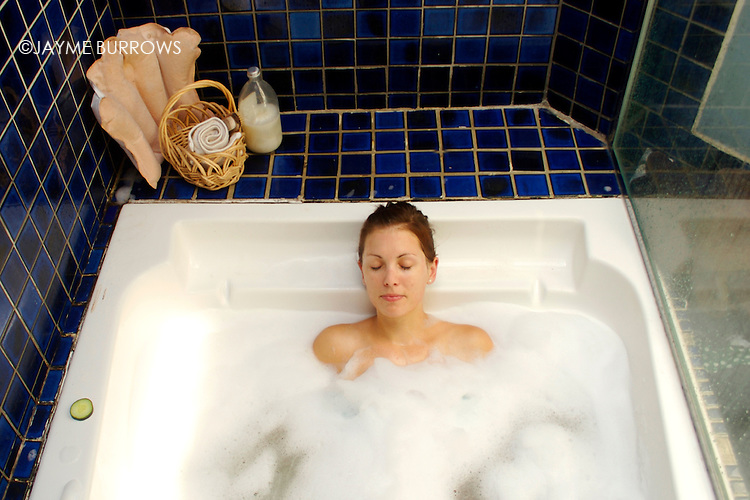 An attractive young lady relaxing in a bubble bath.