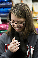 NWA Democrat-Gazette/CHARLIE KAIJO Volunteer Jayde Warden of Rogers pets a cat during a cat adoption event, Sunday, February 10, 2019 at Pet Supplies Plus in Rogers. <br />