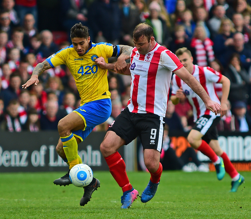 Lincoln City's Matt Rhead vies for possession with Torquay United's Aman Verma<br /> <br /> Photographer Andrew Vaughan/CameraSport<br /> <br /> Vanarama National League - Lincoln City v Torquay United - Friday 14th April 2016  - Sincil Bank - Lincoln<br /> <br /> World Copyright &copy; 2017 CameraSport. All rights reserved. 43 Linden Ave. Countesthorpe. Leicester. England. LE8 5PG - Tel: +44 (0) 116 277 4147 - admin@camerasport.com - www.camerasport.com