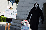 """August  22, 2012, Tokyo, Japan - A Grim Reaper character beats a baby seal prop in from of the Canadian Embassy in downtown Tokyo. Activists of the """"People for Ethnical Treatment of Animals"""" (PETA) protest to stop Canada's unethical bloody seal slaughter whereas the European Union and the United States have already banned the use of seal products. (Photo by Christopher Jue/AFLO)"""