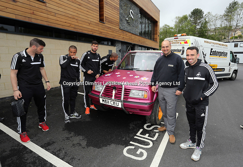 Pictured L-R: Players Alvaro Vasquez, Wayne Routledge, Jordi Amat, Ashley Williams, new owner Leigh Evans and player Leon Britton with the Suzuki Samurai at the Landore Training Ground. Saturday 10 May 2014<br /> Re: Leigh Evans of Leigh Enterprise Tyres is the new owner of &quot;the pink Ferrari&quot;, an old Suzuki Samurai 4x4 car used by Swansea City FC players during the last season.