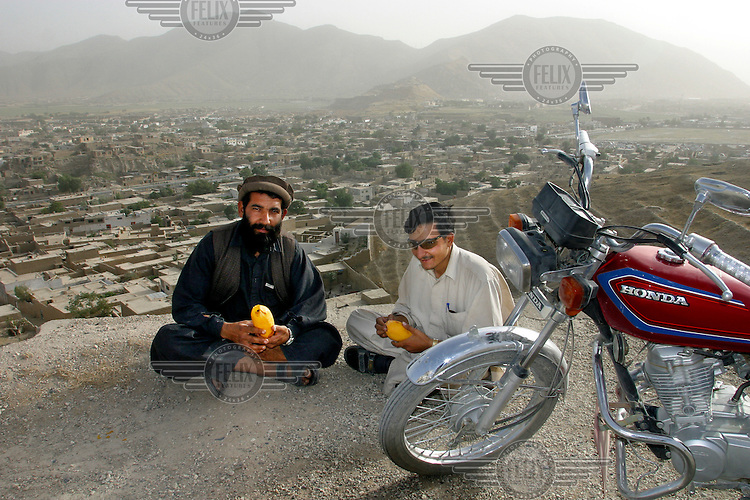 Two men stop on a hill overlooking the city to eat some fruit. Kabul,Afghanistan,Asia.