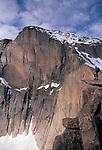 Hiker alone on rock ledge near Diamond (East Face) of Longs Peak, Rocky Mtn Nat'l Park, CO