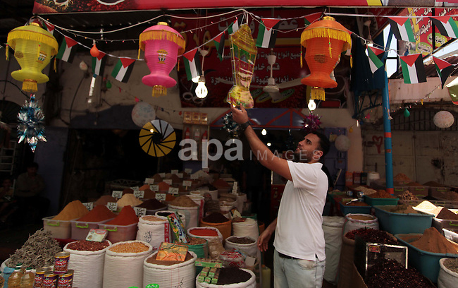 A Palestinian man sells spices in his shop at a market in Gaza City, as Muslims prepare for the upcoming holy fasting month of Ramadan, on June 28, 2014. on the eve of the start of the Muslim holy month of Ramadan. During Ramadan, Muslim believers abstain from eating, drinking, smoking and having sex from dawn until sunset. Ramadan is sacred to Muslims because it is during that month that tradition says the Koran was revealed to the Prophet Mohammed. Photo by Ashraf Amra
