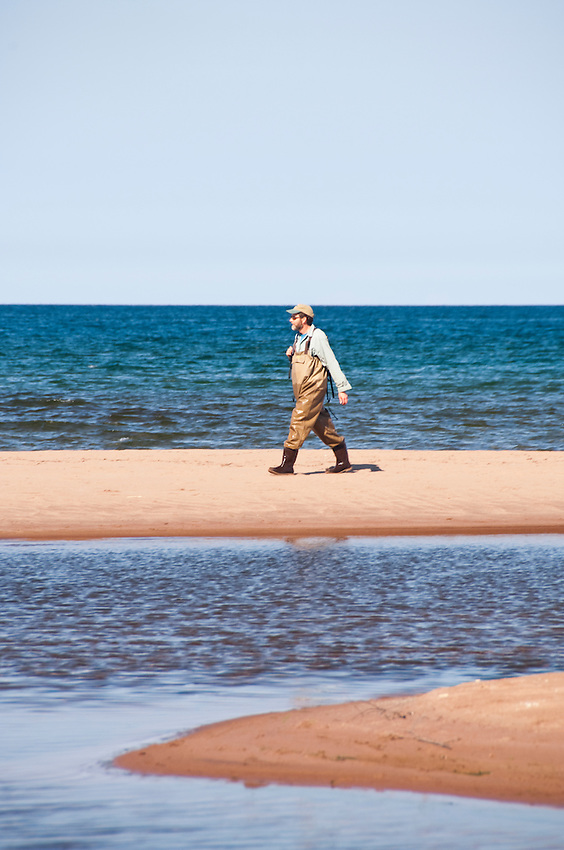 Coaster brook trout researcher Dr. Casey Huckins walks along the beach at the mouth of the Salmon Trout River at Lake Superior near Big Bay Michigan.