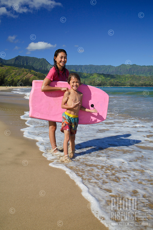 Two local siblings share a boogie board at Hanalei Beach on Kaua'i.