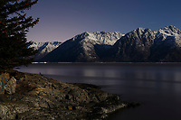 winter landscape of moonlight on Chugach Mountains   above Turnagain Arm with Seward highway at base January 2014