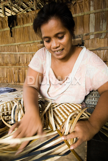 Arawata Narwaia weaves a tradtional mat from sago palm leaves. Leaves dry light or dark depending on exposure to sunlight. Micronesian Gilbert Islanders resetted at Waghena weave more intricate mats than the indigenous Melanesians. Craig Leiisher's MPA and poverty study found that traditional weaving is on the rise in Waghena since the establishment of the Arnavons reserve. Mats are produced for sale and this year many villages are weaving mats to be distributed as aid for tsunami victims.