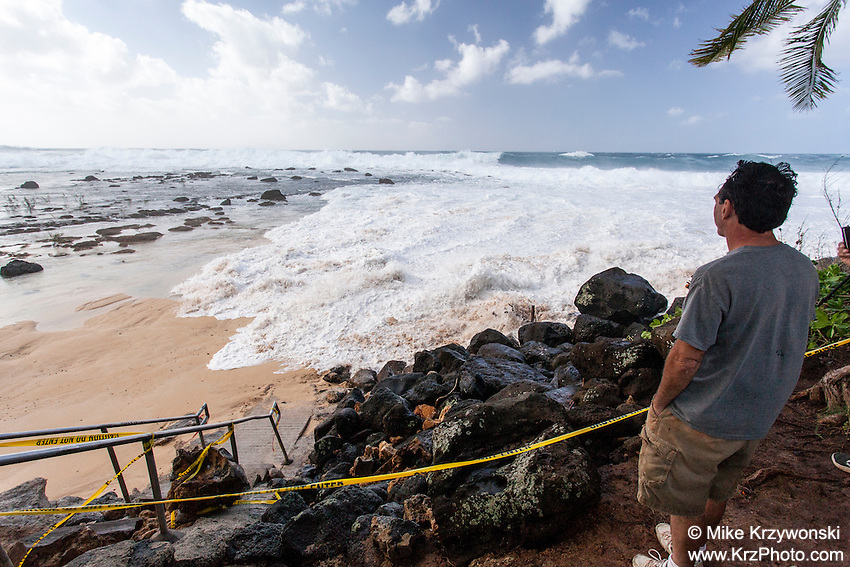 A spectator watching waves approaching public beach access stairs during the giant swell of Jan. 22, 2014 at Keiki Beach, North Shore, Oahu