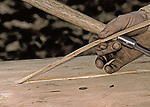 A Wood-Canner peeling up a strip of Cane to use in a chair.