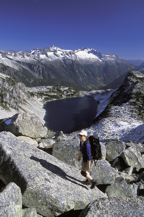 Hiker scrambling up rocks above Hidden Lake, Hidden Lake Trail, North Cascades National Park, Cascade Mountains, Washington