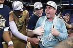 14 March 2015: Notre Dame head coach Mike Brey wears the net he cut down while celebrating with Pat Connaughton (center) and Zach Auguste (30). The Notre Dame Fighting Irish played the University of North Carolina Tar Heels in an NCAA Division I Men's basketball game at the Greensboro Coliseum in Greensboro, North Carolina in the ACC Men's Basketball Tournament quarterfinal game. Notre Dame won the game 90-82.