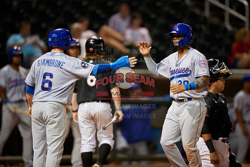 Tennessee Smokies right fielder Eddy Martinez (20) is congratulated by Trent Giambrone (6) after hitting a home run in the top of the seventh inning during a game against the Birmingham Barons on August 16, 2018 at Regions FIeld in Birmingham, Alabama.  Tennessee defeated Birmingham 11-1.  (Mike Janes/Four Seam Images)