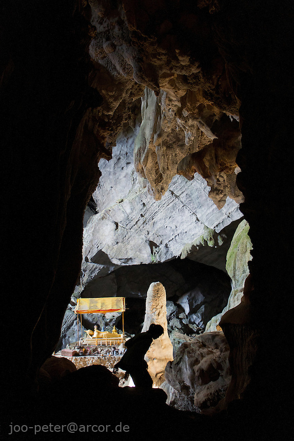 woman climbing down to the great hall in Poukham cave close to Vang Vieng, Laos, 2012. The cave is also spelled  Tham Pu Kham or Tham Pou Kham in latin  letter writing, meaning cave of the golden crab. Like in many caves of  Laos, there is a buddhist shrine inside.