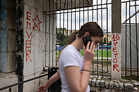 Albania. Gjirokastër. Town center. A teenage woman talks  on her mobile phone while walking by Gjirokastra Stadium. The stadium is a multi-use stadium but it is  mostly used for football matches. It s the home ground of KS Luftëtari Gjirokastër which competes in the Albanian Superliga.  Witten graffitis on the wall of a red communist star and the name of Enver. Enver Halil Hoxha (16 October 1908 – 11 April 1985) was an Albanian communist politician who served as the head of state of Albania from 1944 until his death in 1985, as the First Secretary of the Party of Labour of Albania. He was born in the city of Gjirokastër. He was chairman of the Democratic Front of Albania and commander-in-chief of the armed forces from 1944 until his death. Gjirokastër is a city in southern Albania. 23.05.2018 © 2018 Didier Ruef
