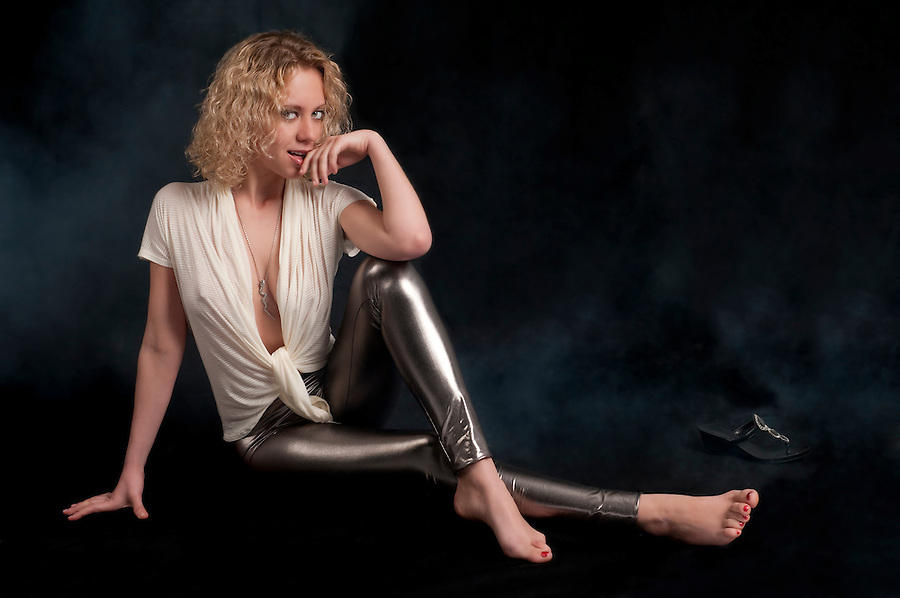 Young caucasian woman with curly hair seated with sensual pose.