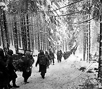American soldiers of the 289th Infantry Regiment march along the snow-covered road on their way to cut off the St. Vith-Houffalize road in Belgium.  January 24, 1945.  Richard A. Massenge.  (Army)<br /> NARA FILE #:  111-SC-199406<br /> WAR &amp; CONFLICT BOOK #:  1079