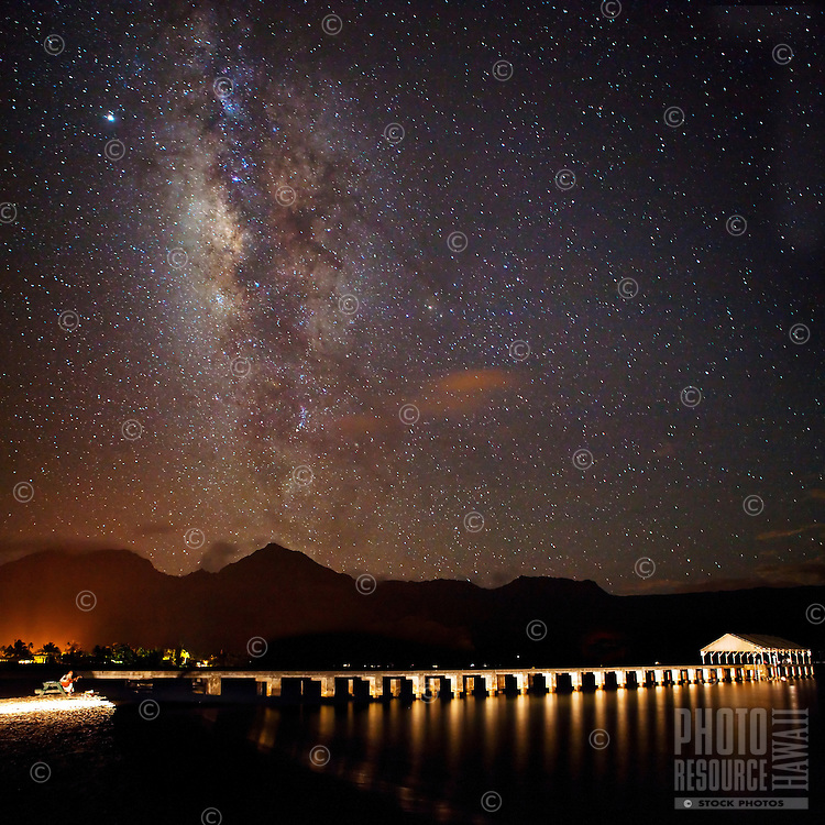 A musician plays a guitar near the pier at historic Hanalei Bay as the Milky Way seems to rise above Kaua'i on a very dark clear night.