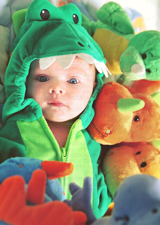 Closeup of a newborn baby with blue eyes in a dinosaur costume surrounded in dinosaur stuffed animals.